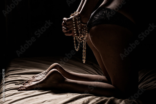 Sensual photo of woman with tied hands in bedroom