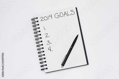 Fotografia  Text 2019 goals on notepad with pen on white background, office desk