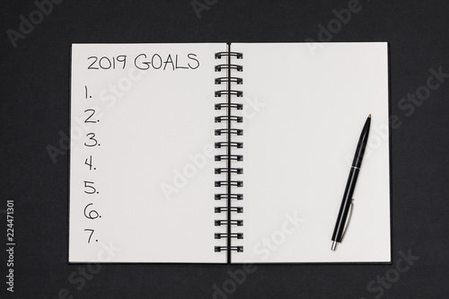 Fotografia  Text 2019 goals on notepad with pen on black background, office desk