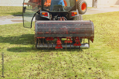 Fotografie, Tablou Gardener Operating Soil Aeration Machine on Grass Lawn