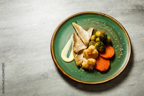 Fotografía  top view on tasty hake fillet with vegetables and sauce served on green plate