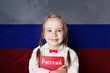 Leinwandbild Motiv Learn russian language. Child girl student with book against the russian flag background