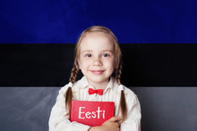 Estonian Language Concept With Litte Girl Student With Book Against The Estonian Flag Background. Learn Language