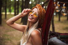 Photo Of Pretty Hippy Woman, Wearing Stylish Accessories Smiling While Resting In Forest Camp
