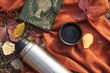 Thermos with hot tea in the forest. Concept picnic in the park.