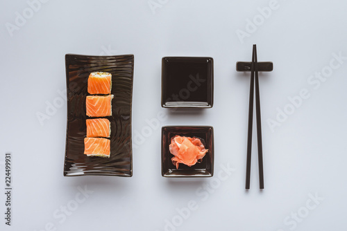 Photo  top view of delicious sushi with salmon, ginger, soy sauce and chopsticks isolat