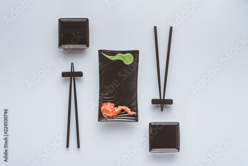 Fotografia  top view of chopsticks and wasabi with ginger for eating sushi isolated on white
