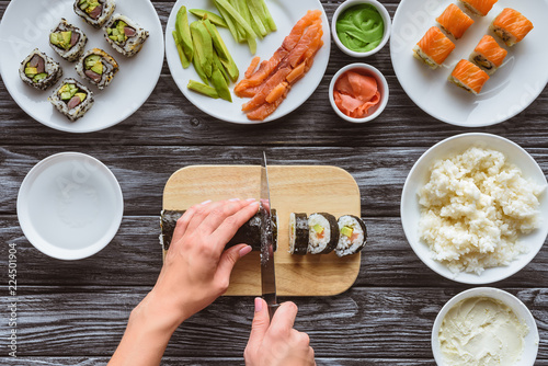 Photo  partial top view of person cutting delicious sushi roll with knife