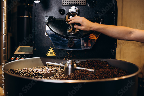 Fotografija Freshly roasted coffee beans pouring from a large coffee roaster into the cooling cylinder