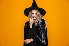 Image Of Tricky Witch Woman Wearing Black Costume And Halloween Makeup Looking At Camera, Isolated Over Yellow Background