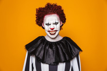 Angry Clown Man 20s Wearing Black Costume And Halloween Makeup Looking At Camera, Isolated Over Yellow Background