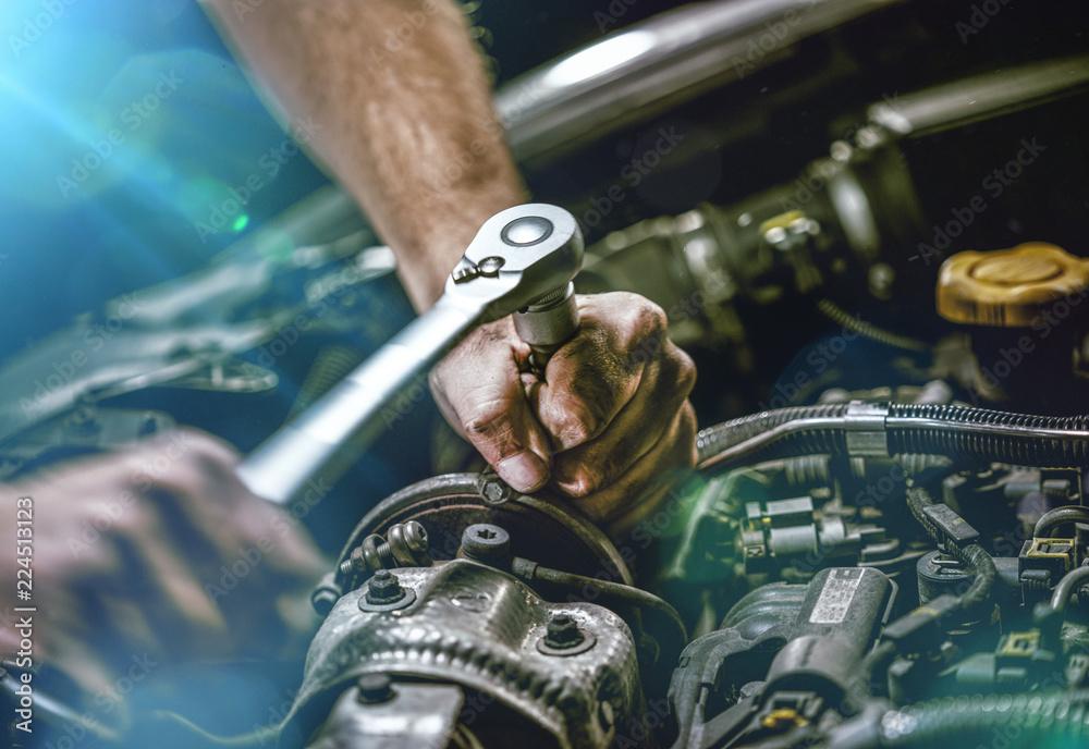 Fototapeta Auto mechanic working on car engine in mechanics garage. Repair service. authentic close-up shot