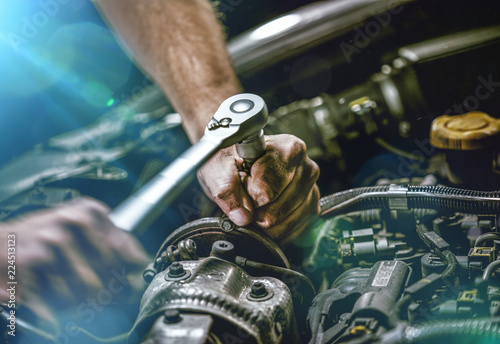 plakat Auto mechanic working on car engine in mechanics garage. Repair service. authentic close-up shot