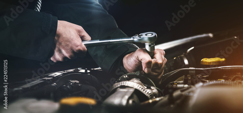 Auto mechanic working on car engine in mechanics garage. Repair service. authentic close-up shot