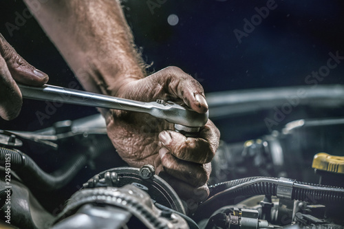 Leinwand Poster Auto mechanic working on car engine in mechanics garage