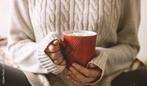 Fotografie, Obraz  Women's hands in sweater are holding cup of hot coffee, chocolate or tea