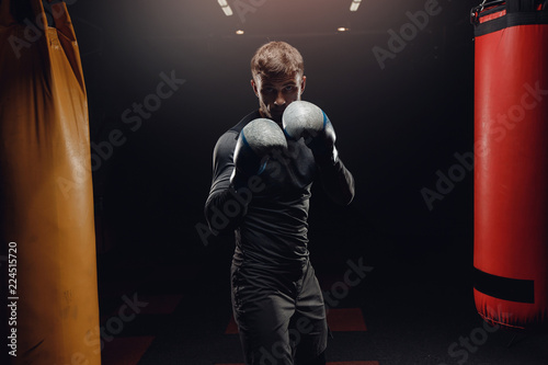 Photo Male boxing in punching bag. Training man in gym.