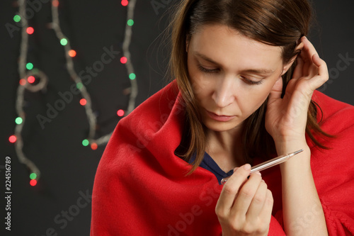 Foto  Young woman wrapped in warm red coverlet holds thermometer which shows high temp
