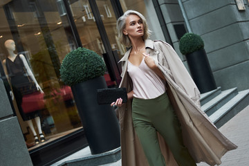 Fashion. Young stylish woman walking on the city street looking aside curious