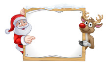 Santa Claus And Reindeer Christmas Cartoon Characters In A Pointing At A Snow Covered Sign