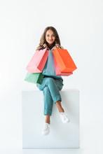 Smiling Shopaholic Sitting On White Cube With Shopping Bags, Isolated On White