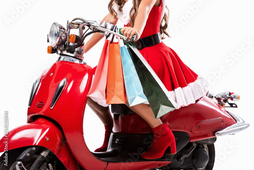 Scooter cropped view of girl in santa claus costume driving red scooter with shopping bags, isolated on white