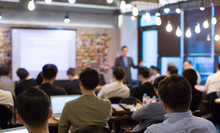 Business People Meeting And Working While Business Executive Lead Presenter Speaks To Group Of Successful Technology Entrepreneurs. Consultant Advisor. Growth Training Lecture. Defocused Blurred