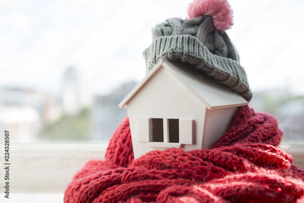 Fototapety, obrazy: house in winter - heating system concept and cold snowy weather with model of a house wearing a knitted cap