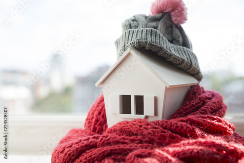 Obraz house in winter - heating system concept and cold snowy weather with model of a house wearing a knitted cap - fototapety do salonu