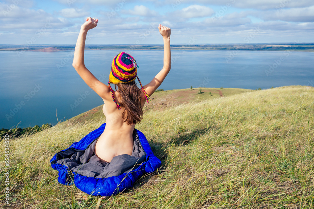 Fototapety, obrazy: Back view of sexy naked woman tourist in a funny hat from Nepal sitting in blue sleeping bag on the grass, enjoying sunny morning in the mountains lake.