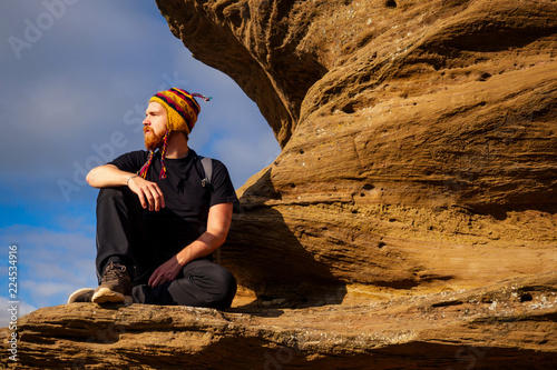 Man brave red-haired beard climbing bouldering stone rock tourist climbs up with Canvas Print