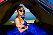 Back View Of Sexy Naked Woman Tourist In A Funny Hat From Nepal Sitting In Blue Sleeping Bag In A Tent Sunny Good Morning In The Mountains Lake.