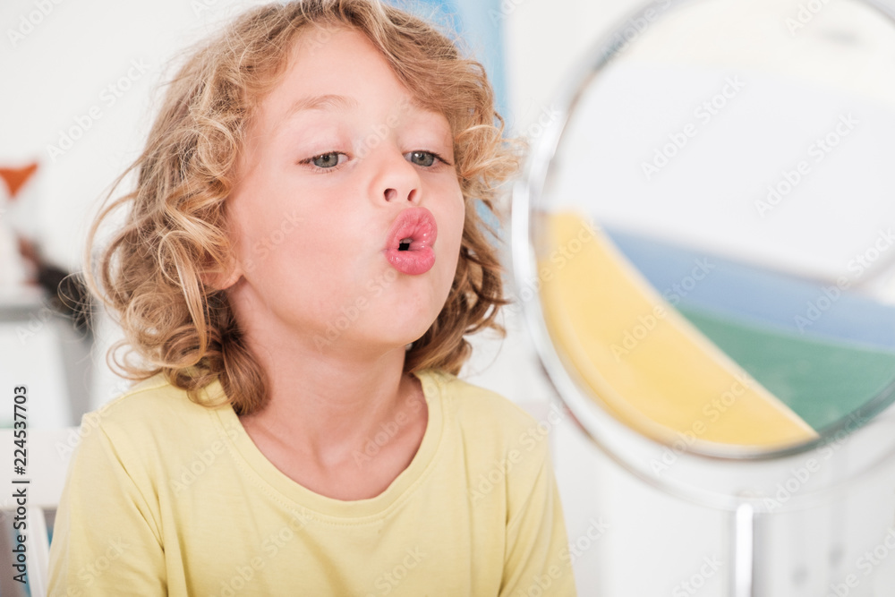 Fototapeta Kid learning to speech in front of window during correct pronunciation classes