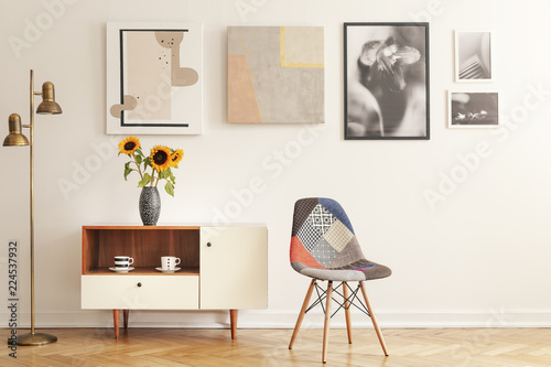 Photo Colorful chair standing in white living room interior with gallery on wall, cupb