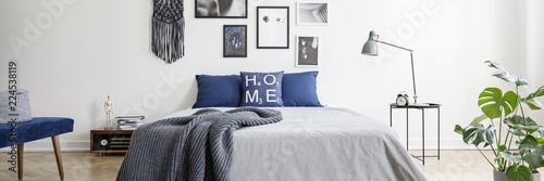 Fényképezés  Real photo of a navy blue bedroom interior with a double bed, pillows and graphi