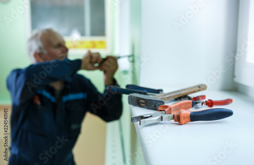 Fotografie, Obraz  middle-aged senior man worker is working indoors fixing fitting screwing repairi