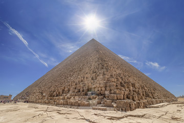 The Pyramid of Cheops illuminated by the sun in backlight, with people entering inside to visit it. The area with the great pyramids of Giza, Egypt