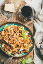 Italian Traditional Pasta Dinner. Flat-lay Of Tagliatelle Bolognese With Minced Meat, Tomato Sauce And Parmesan Cheese And Glass Of Red Wine Over Rustic Wooden Board Background, Top View