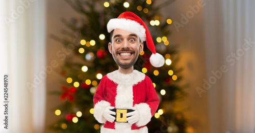 Valokuva  holidays, expression and people concept - smiling man with funny face in santa c