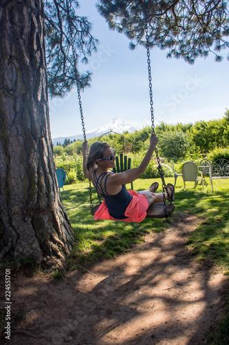 Fotografija  Adult woman swinging on a wooden tree swing in Mt