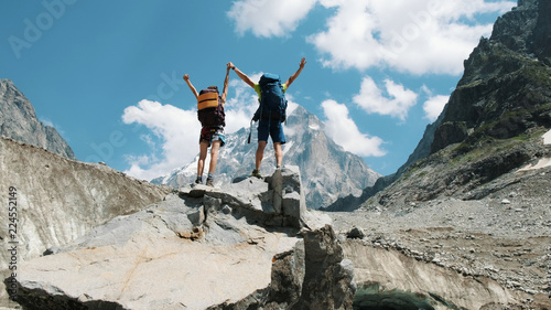 Fotografia Couple of tourists with backpacks in the campaign raise their hands up on the top of the mountains
