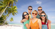travel, tourism and summer holidays concept - group of happy smiling friends in sunglasses hugging over tropical beach background in french polynesia