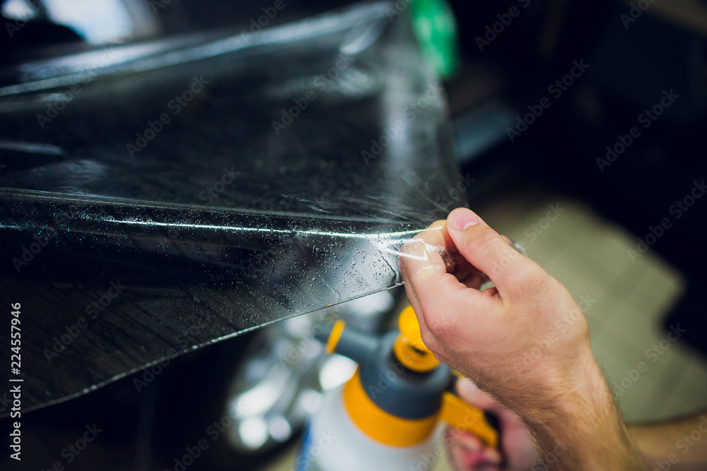 Fototapety, obrazy: Worker hands installs car paint protection film wrap.