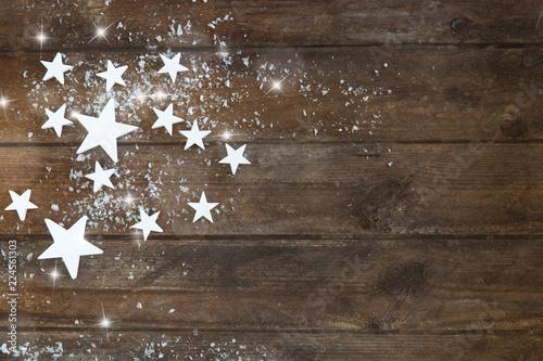 Fototapeta  Weihnachtsdekoration mit Sternen auf braunem Holzhintergrund,Weihnachtskarte