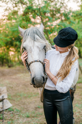 Beautiful young girl with light hair in uniform competition hugs her horse : outdoors portrait on sunny day on sunset in autumn
