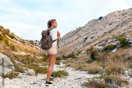 Fototapeta Hiker girl with backpack on hiking trail in mountain, trekking and travel lifestyle concept obraz