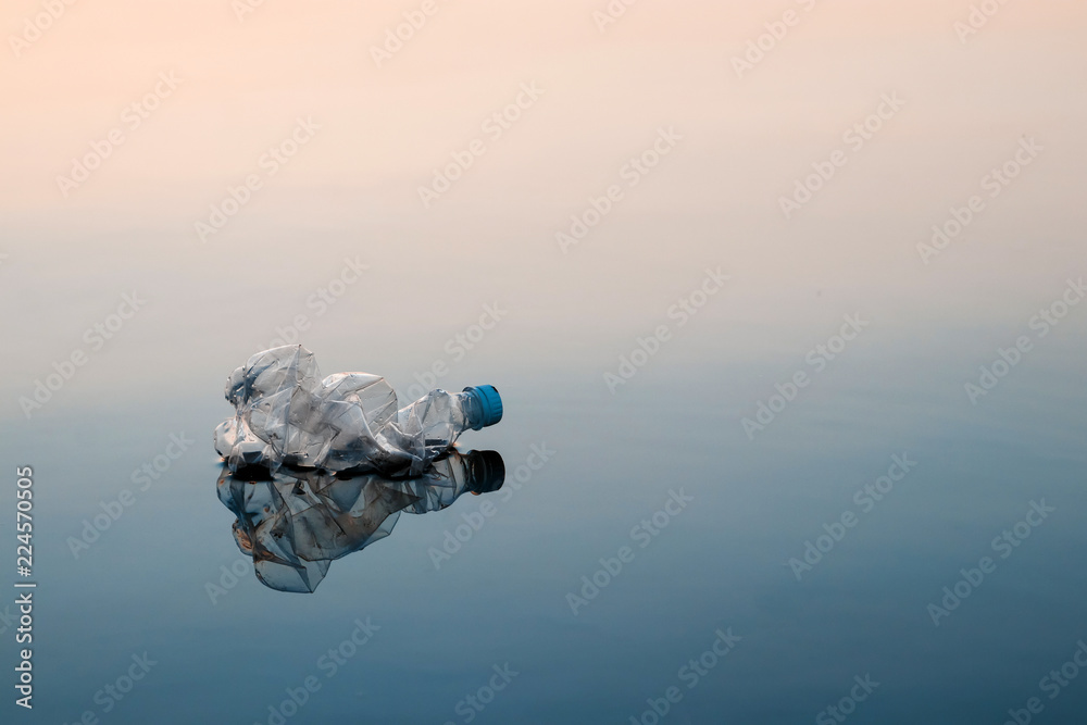 Fototapety, obrazy: Concept of pollution, creative background. A plastic bottle floating in the ocean, non-decomposable plastic, pollution of the environment. Copy space.