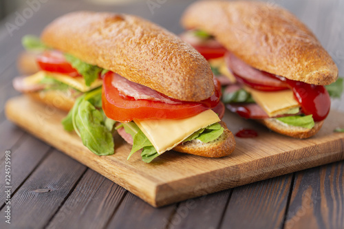 Staande foto Snack Two baguette sandwiches with salami, cheese, arugula salad, tomatoes and onion on a cutting board. Sandwiches on dark wooden background. Tasty snack.