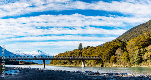 Fotobehang Wit Panorama view, a Stunning landscape of the snow mountain and a bridge across the river. Blue sky and some cloudy.