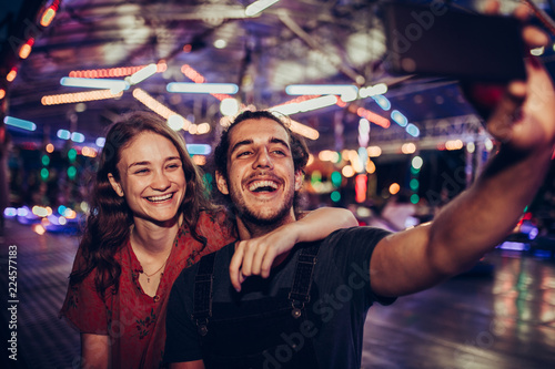 Young happy couple/ Young happy couple enjoying themselves at the amusement park - 224577183